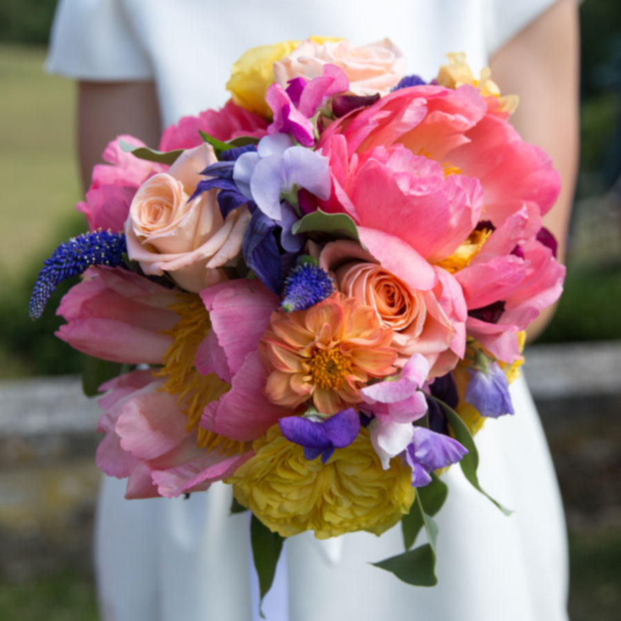 A colourful summer bridal posy with roses, dahlias, peonies and sweet peas