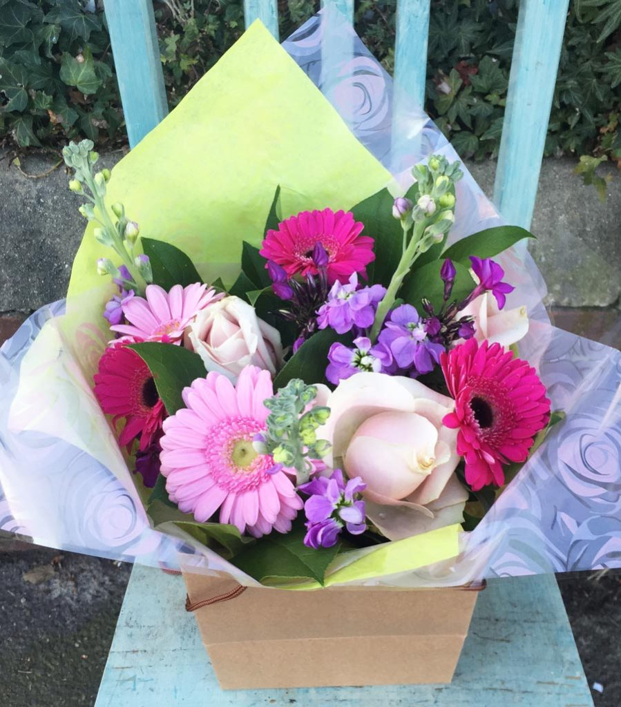 A Mothers Day Spring bright and cheerful hand-tied bouquet in aquapack and gift bag, with roses, stocks, phlox and germini